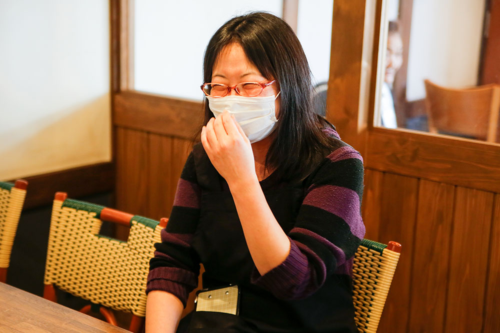 マスクに手を当てて笑う石川さん