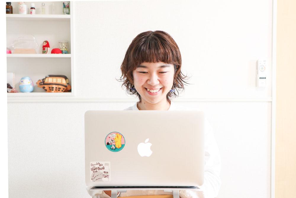 パソコンの前で笑顔で仕事するくぼちー