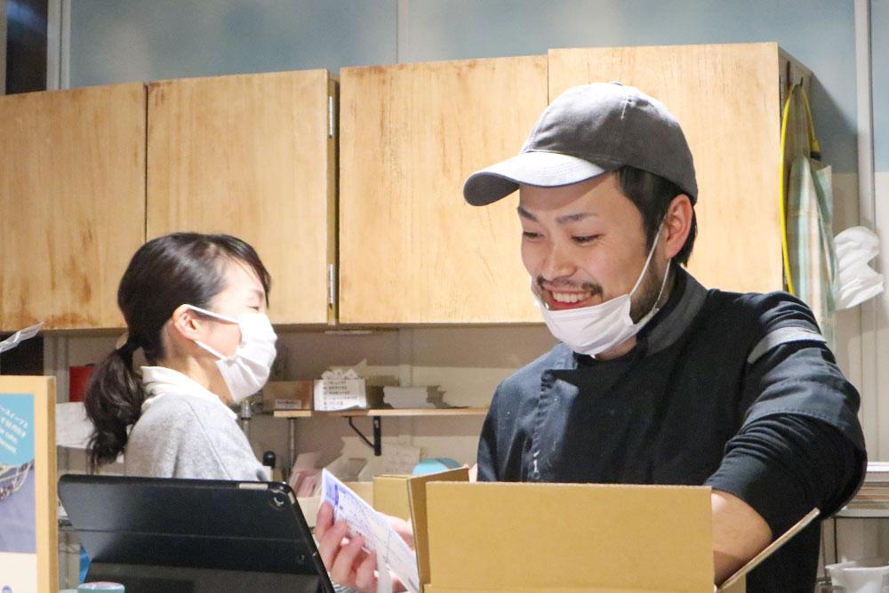笑いながら梱包作業をする加藤泰